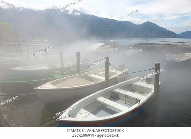 Small port on Alpine lake Maggiore with boats in the fog and Swiss Alps in Ascona, Switzerland