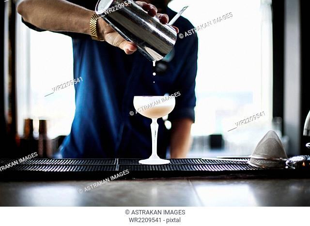 Midsection of bartender pouring cocktail from shaker in restaurant