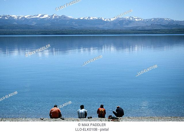 Four Men Sitting at the Edge of a Lake with the Snow-Capped Mountains in the Background  Lake Nahuel Huapi, Bariloche, Lake District, Argentina, South America