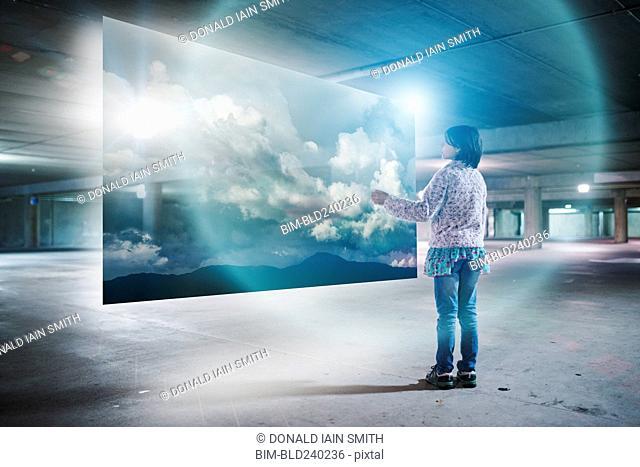 Mixed Race girl watching clouds on virtual screen in parking garage