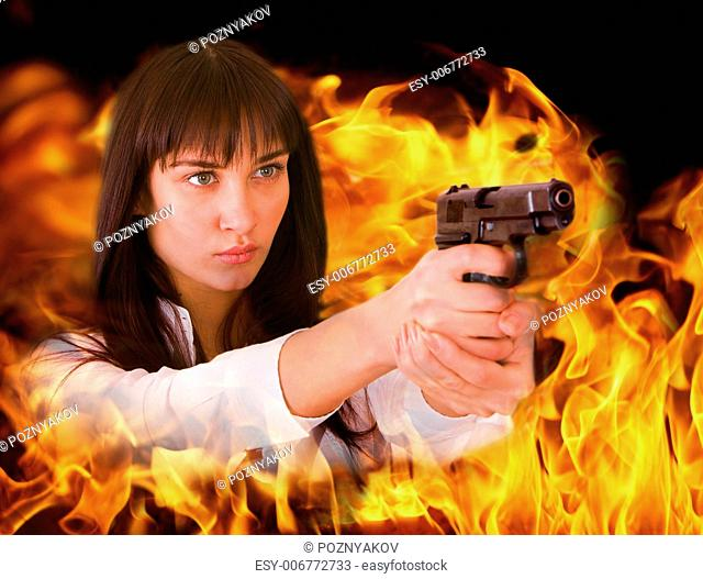 Aggressive girl shoots from flame. Collage