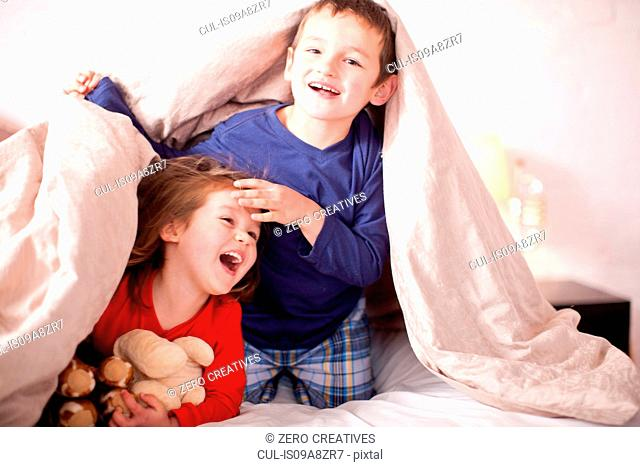 Two young children playing under duvet