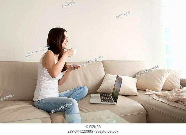 Young woman drinking coffee while sitting comfortably at home sofa, happy teen relaxing with laptop computer, relaxed girl enjoying spending time alone watching...