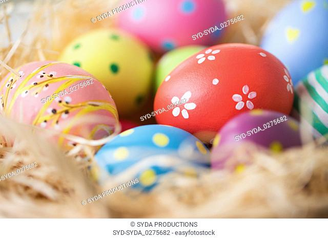 close up of colored easter eggs in straw
