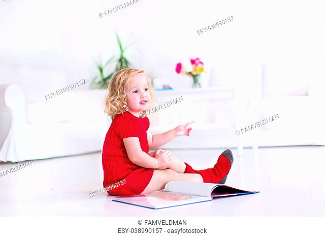 Cute little girl with curly hair wearing a warm knitted red dress and socks reading a book sitting on the floor in a white living room