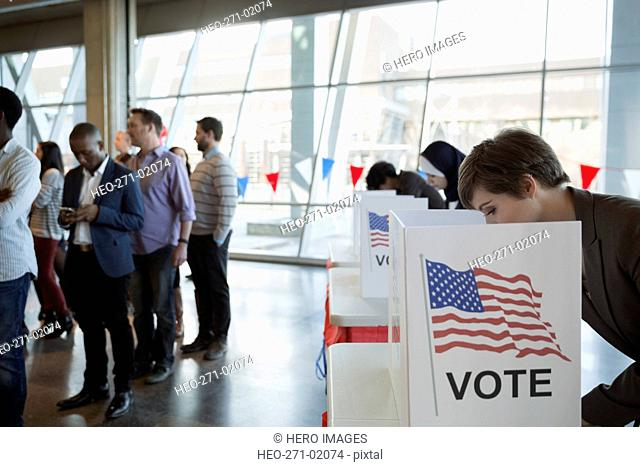 Young woman in voting booth at polling place