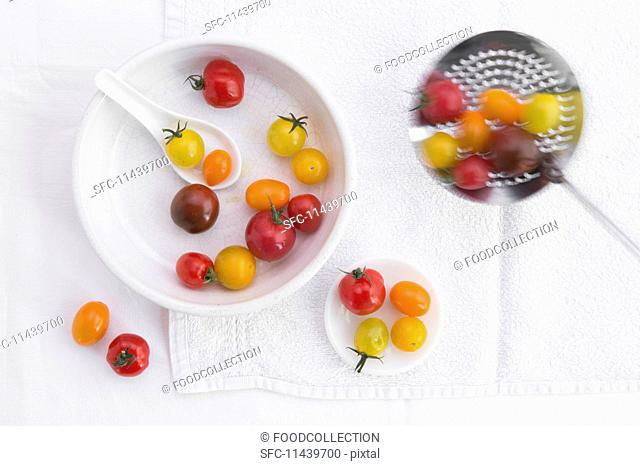 Various different coloured tomatoes in a porcelain bowl and on a draining spoon