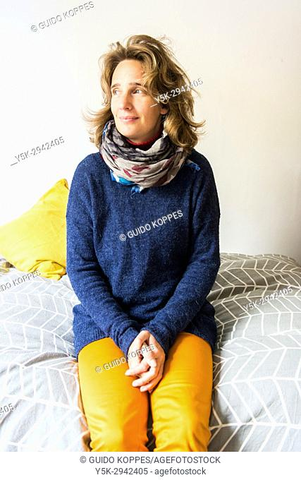 Tilburg, Netherlands. Portrait adult blonde woman sitting on the Airbnb guest room bed