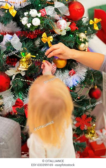 Baby decorating Christmas tree. Rear view
