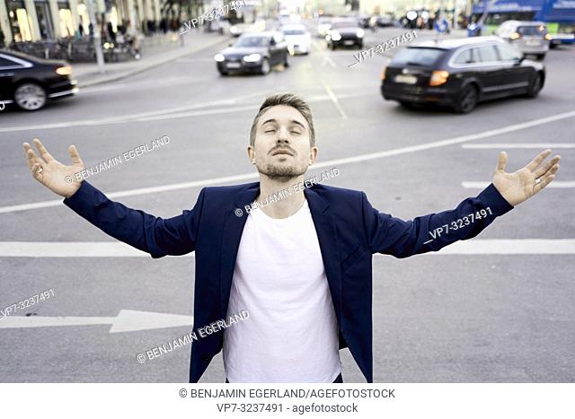 business man with open arms at street in city next to traffic, calm relaxed waiting, contemplative, in Munich, Germany