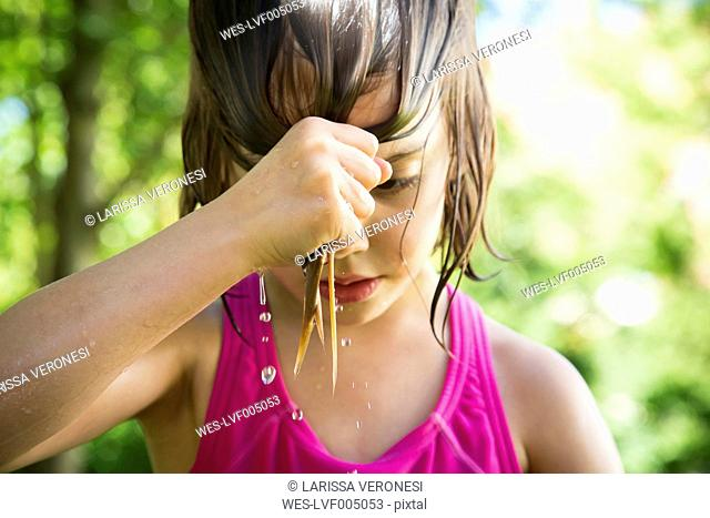 Little girl wringing out her wet hair