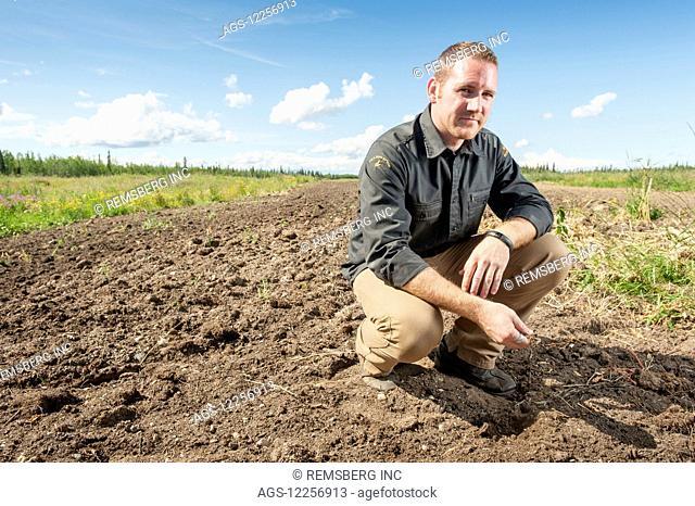 Portrait of barley farmer kneeling over tilled field; Delta Junction, Alaska, United States of America