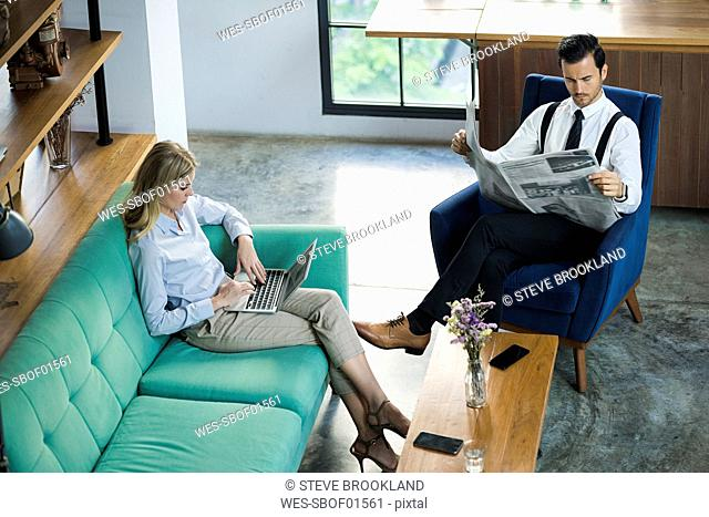Business colleagues with laptop and newspaper in coworking space