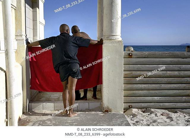 Rear view of a man holding a towel in front of a woman changing clothes, Muizenberg, False Bay, Cape Town, Western Cape Province, South Africa