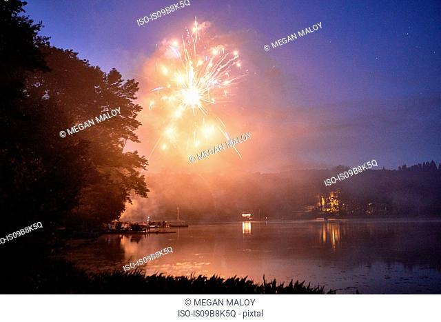 Fireworks exploding over lake at dusk