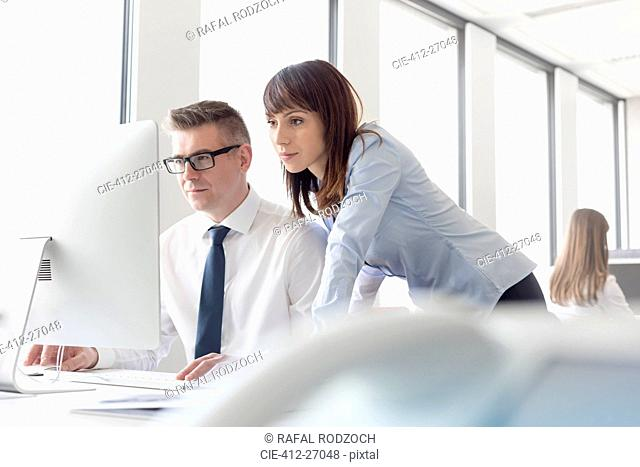 Focused businessman and businesswoman working at computer in office