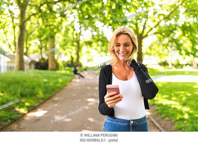 Mature woman strolling in park looking at smartphone