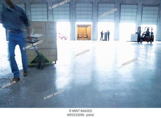 Employees pulling pallets and loading cardboard boxes of products into truck trailers in a distribution warehouse loading dock area