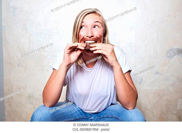 Portrait of woman eating bar of chocolate, chocolate around mouth