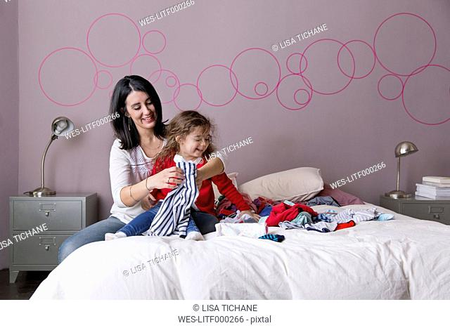 Mother and little daughter folding laundry together on the parents' bed