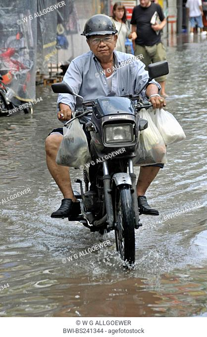 old man riding on a moped with full shopping bags through a street flooded after a heavy shower, Thailand, Bangkok
