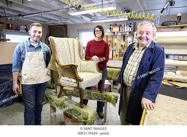 Senior Caucasian man upholsterer and his understudy team of young people working on an antique chair