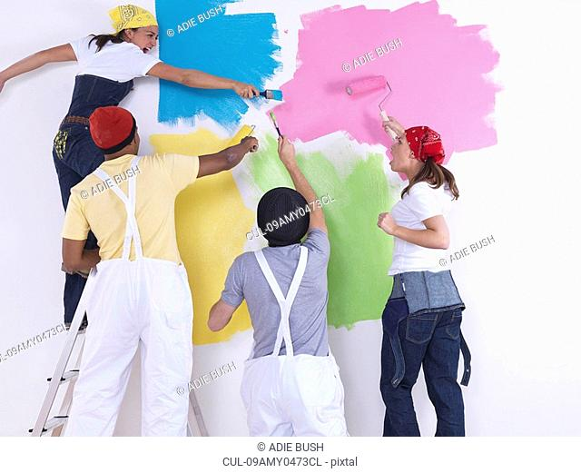 Group of friends painting wall