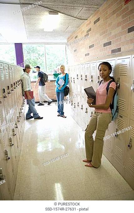Portrait of students standing by lockers in corridor
