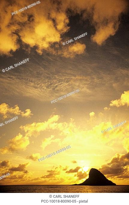 Hawaii, Oahu, Kaneohe, Sun setting behind Chinaman's hat, yellow cloudy sky