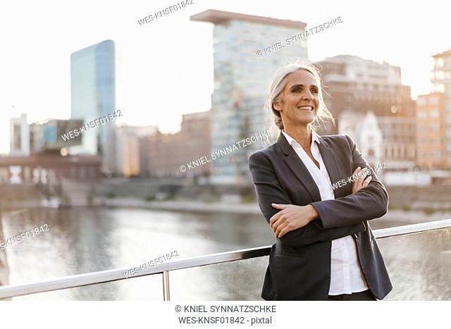 Confident businesswoman standing on bridge