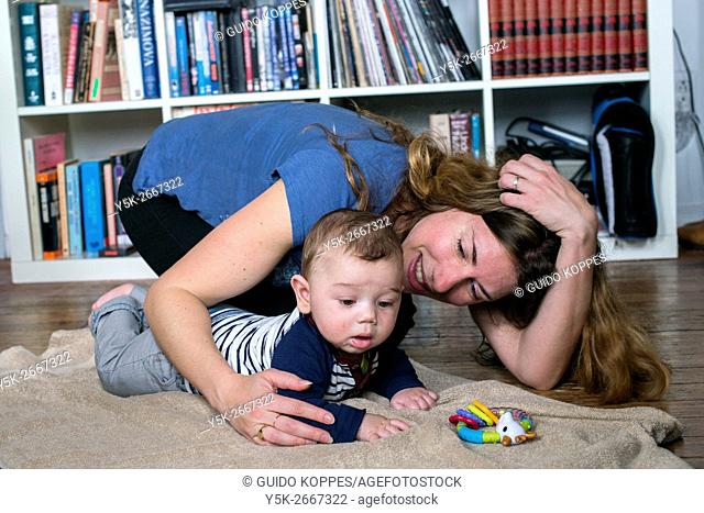 New York City, USA. A mother playing with her fice months old son on the floor of an Airbnb guesthouse