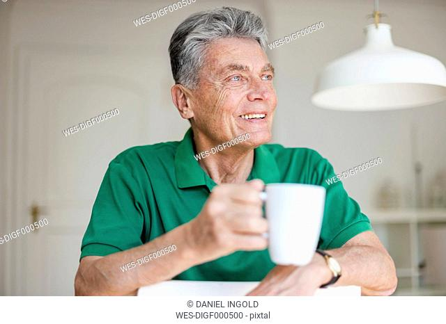 Smiling senior man at home holding cup of coffee