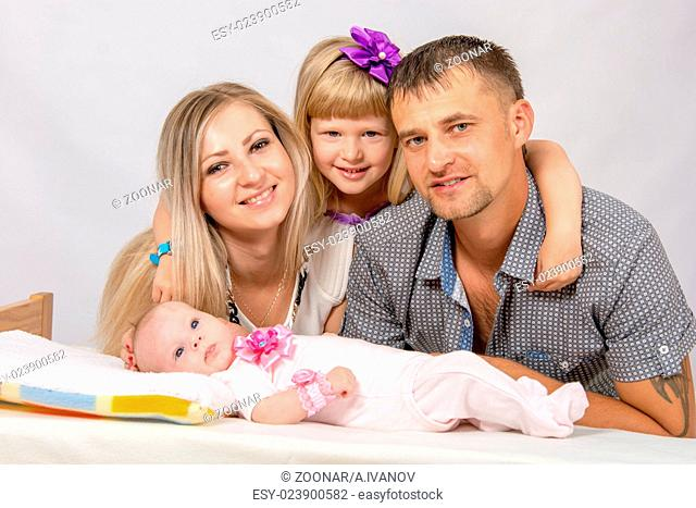 Mother, father, daughter and five-year newborn baby looks in the picture