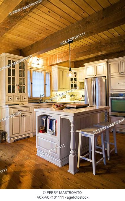 Kitchen with antique style cream white wooden cabinets, island with barstools and stainless steel appliances inside a small cottage style log home, Quebec