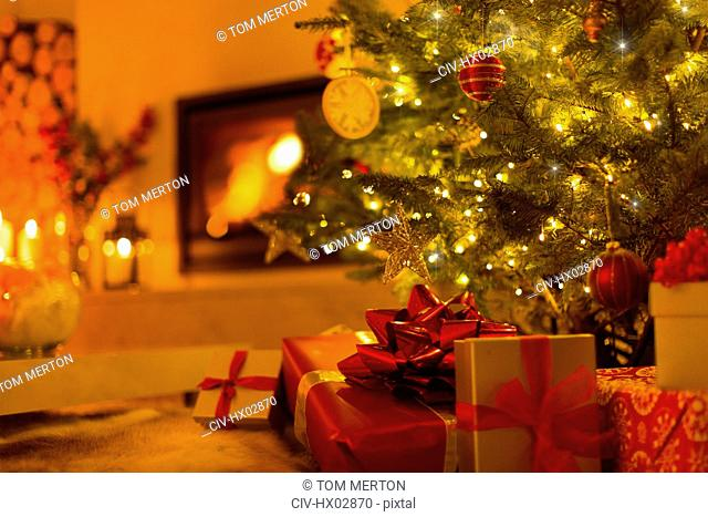 Gifts under Christmas tree in ambient living room with fireplace