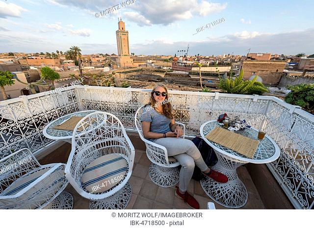 Young woman on a roof terrace, restaurant, view of the old city, mosque with minaret, Marrakech, Morocco