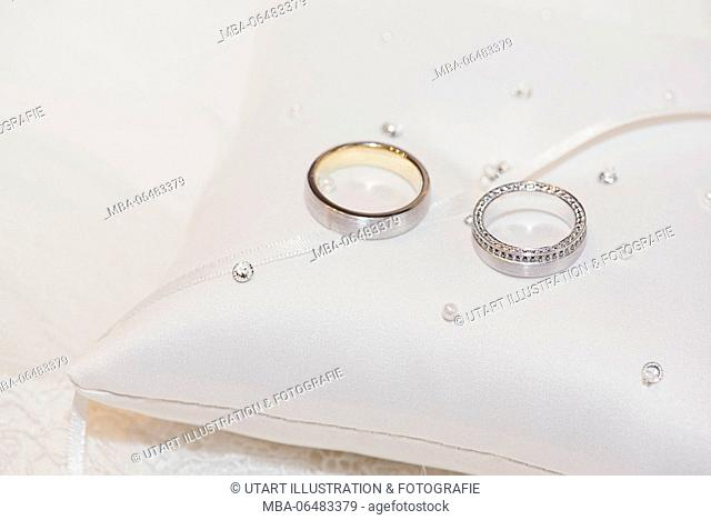 Wedding rings made of gold and platinum with diamonds on a small cushion with pearls