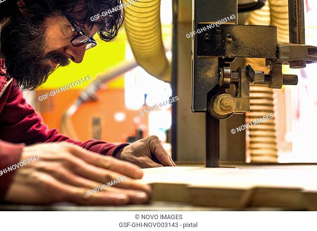 Woodworker Cutting Wood with Band saw