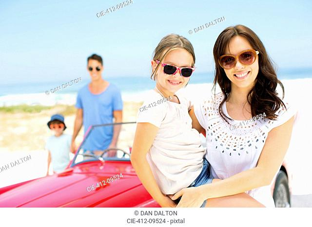 Mother and daughter smiling by convertible on beach