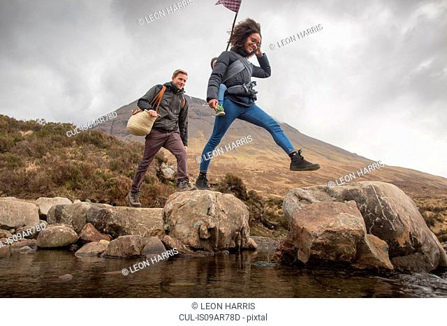Couple crossing river, Fairy Pools, near Glenbrittle, Isle of Skye, Hebrides, Scotland