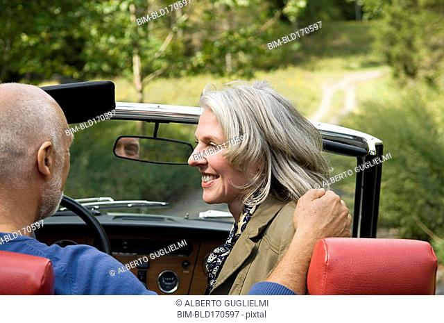 Rear view of older couple driving convertible