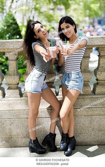 Two happy twin sisters outdoors having a takeaway drink