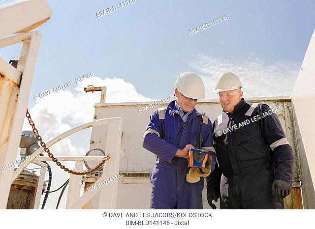 Caucasian technicians working at fuel storage facility
