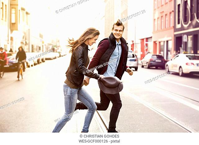 Germany, Berlin, happy couple crossing a street