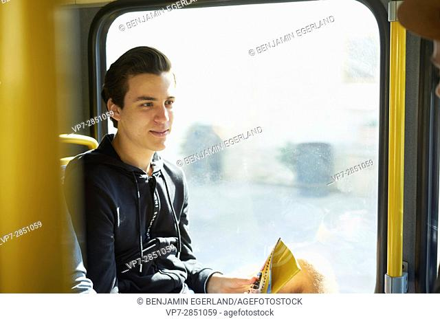 Young man is sitting in public transport