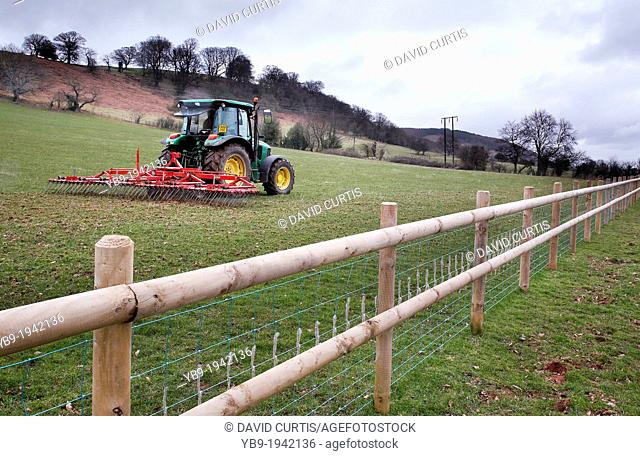 Farmer in tractor, aerating a field with grass harrows attachment on a farm in South Wales, UK