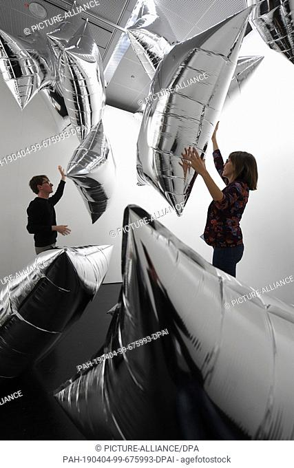 """03 April 2019, Baden-Wrttemberg, Karlsruhe: At the Center for Art and Media (ZKM) are persons in the installation """"""""Silver Clouds"""""""" by Andy Warhol from 1966"""