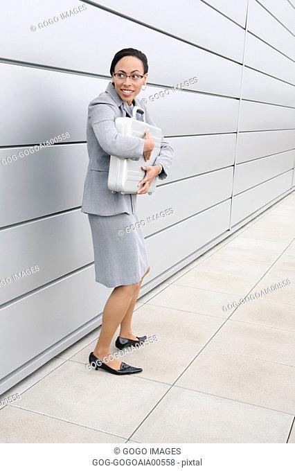 African businesswoman clutching briefcase