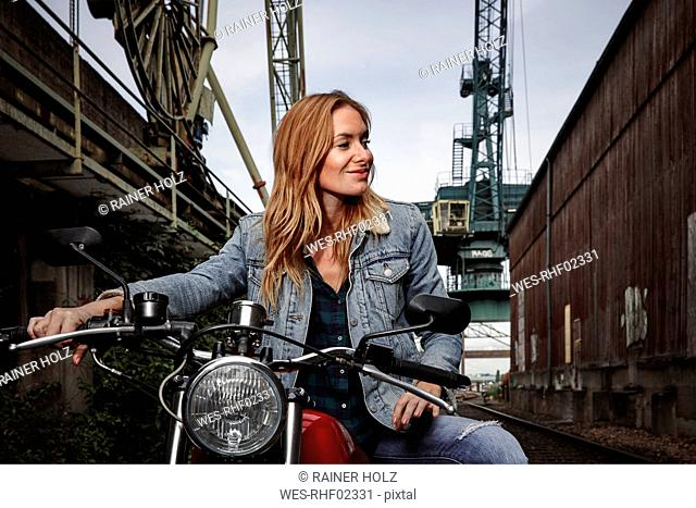 Portrait of smiling young woman on motorcycle