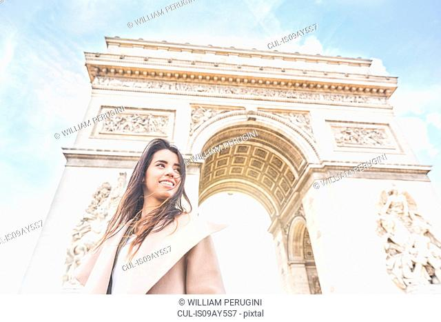 Low angle view of young woman in front of Arc de Triomphe, Paris, France